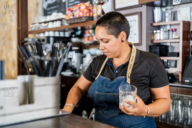 Positive focused female barkeeper in apron standing at counter making alcohol drinks and smiling while working in cafe