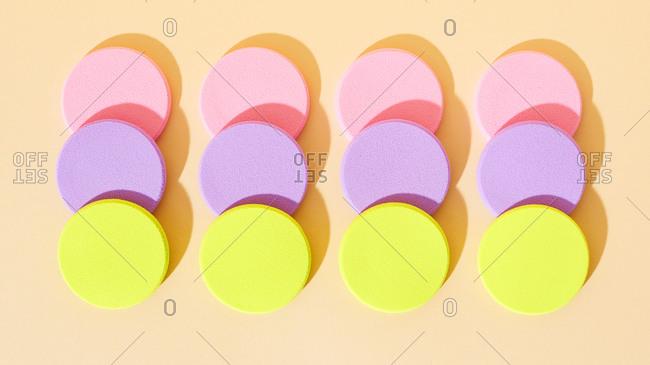 Round pastel makeup sponges arranged on neutral background