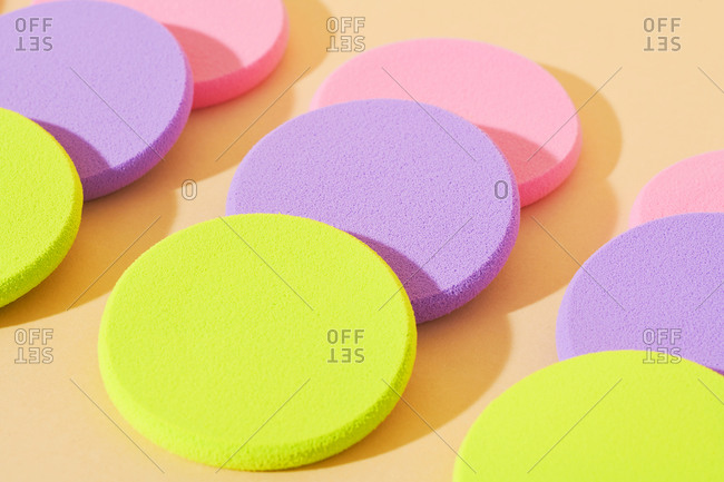 Close up of round pastel makeup sponges arranged on neutral background