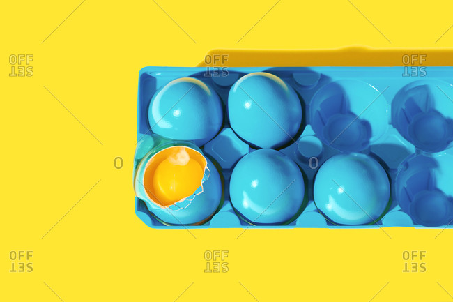 Top view of blue painted eggs on yellow background with one broken