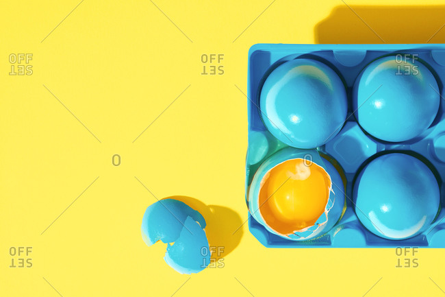 Blue painted eggs on yellow background with one broken