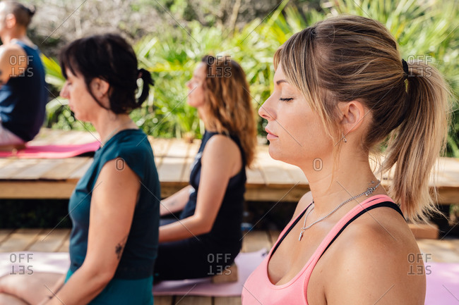 From above group of diverse people meditating in Lotus pose during yoga practice in tropical resort on sunny day