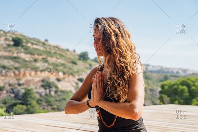 Flexible young female with eyes closed in sportswear sitting on wooden platform in Lotus pose with praying hands while meditating during outdoor yoga practice