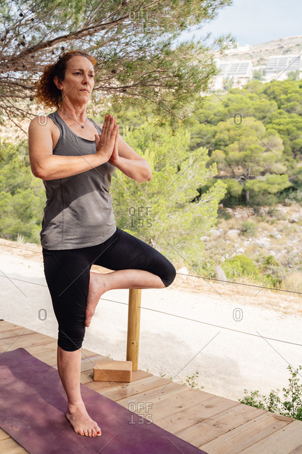 Full body woman in sportswear standing on mat doing Tree pose practicing yoga on wooden platform surrounded by trees and plants on nature in daylight looking away