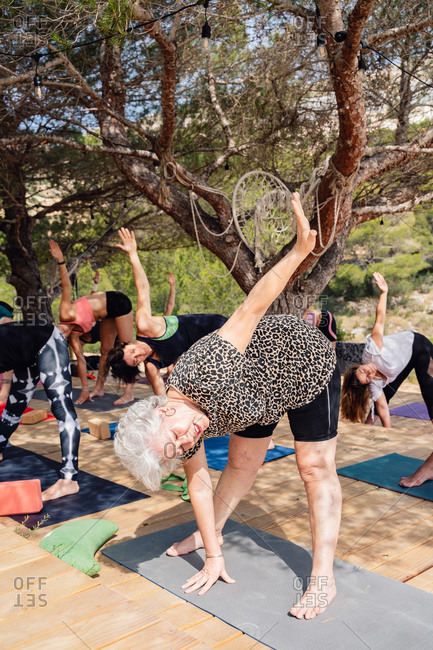 Full body of flexible senior woman in activewear practicing yoga with group of anonymous ladies in park and doing Revolved Wide Legged Forward Bend position