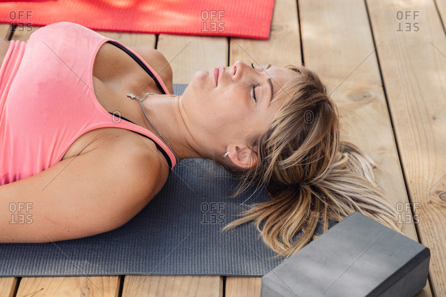 Female relaxing in Corpse asana with eyes closed after finishing outdoor yoga workout on sunny day