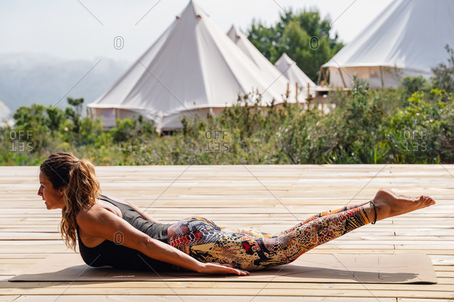 Side view of barefooted fit female in  sportswear strengthens spine muscles while practicing Salabhasana yoga position on wooden platform in camp