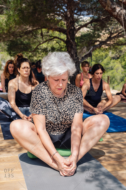 Full length focused mature female doing Bound Angle pose while practicing yoga with other women in open air sitting on wooden podium