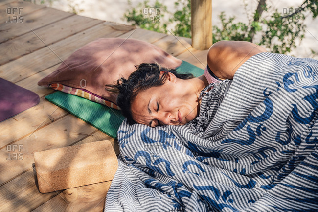 From above of middle aged woman sleeping on mat in garden after outdoor yoga lesson