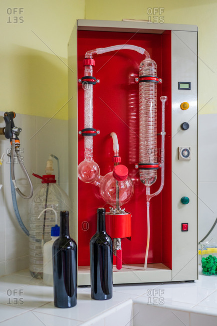Big rectangular wine analysis equipment with transparent tubes on ceramic surface near similar bottles of red wine in laboratory