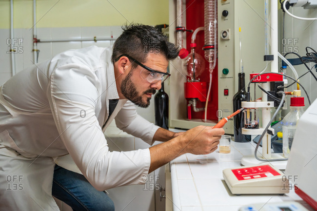 Side view of serious chemist in uniform and protective eyeglasses using transparent flask with red wine and measuring tools at work in lab