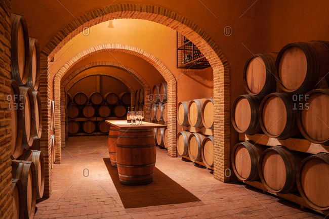 Interior of contemporary spacious winery storage with wooden barrels and cozy table in center for wine tasting