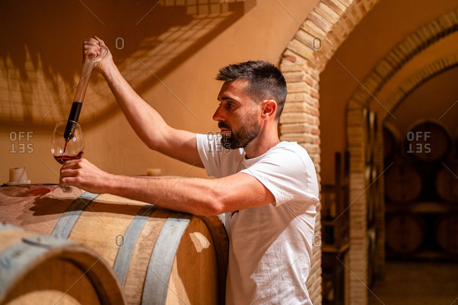 Side view serious male winemaker pouring aromatic red wine from wooden barrel into glass by using special glass tool
