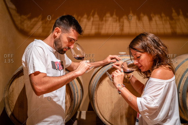 Side view positive couple wearing casual outfits standing near barrels with wine and smelling fragrant red wine in glasses while spending time together in cozy winery