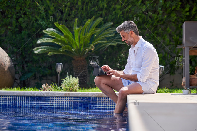 Side view of busy male entrepreneur sitting at poolside with legs in water and browsing netbook while working remotely on sunny day