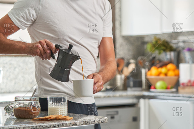 Brutal male in casual wear standing in kitchen and pouring aromatic coffee into mug during breakfast at home
