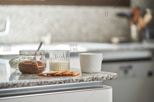 Glass of milk and jar of brown sugar placed on counter with cup of coffee and cookies in modern kitchen