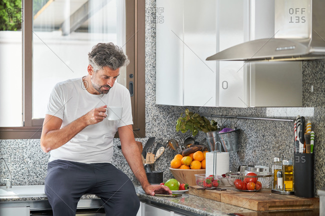 Tranquil male with gray hair sitting on counter in modern kitchen and browsing smartphone while enjoying morning coffee