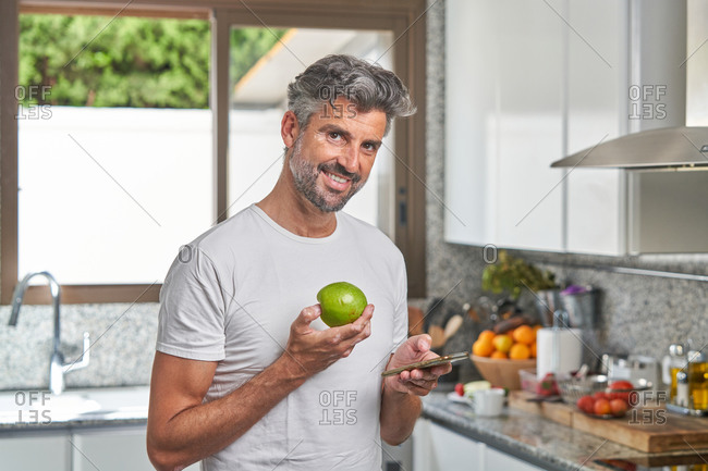 Cheerful mature male in casual t shirt standing in kitchen with green apple and reading message on smartphone during breakfast in morning