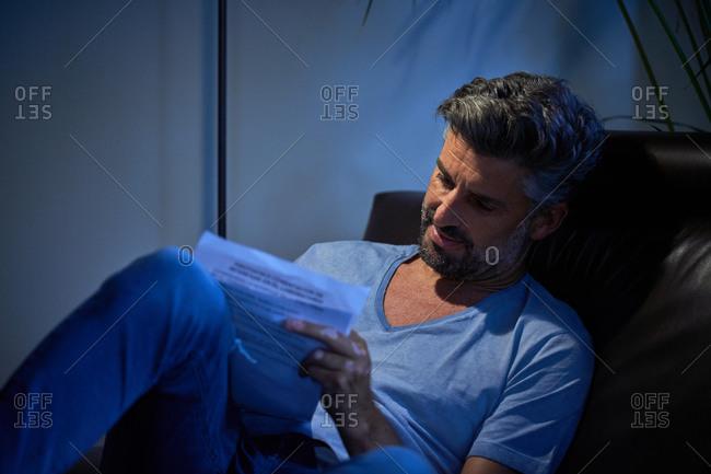 Delighted mature male in casual clothes resting in comfortable armchair and taking notes in notepad