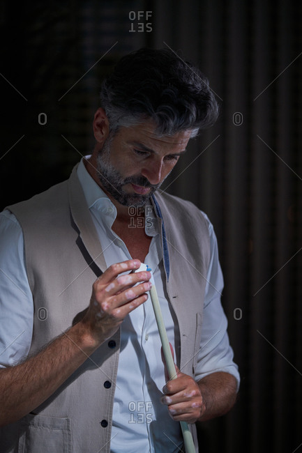 Brutal male standing in dark room and rubbing billiard cue with chalk before game