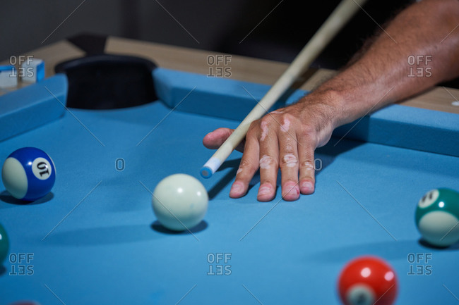 Confident focused gray haired male in white shirt preparing for shot with cue while playing billiards game