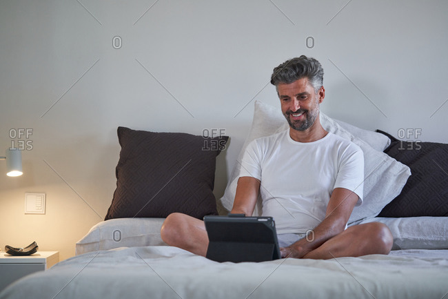 Smiling middle aged bearded male in casual clothes sitting on bed and browsing laptop while resting in cozy bedroom in evening