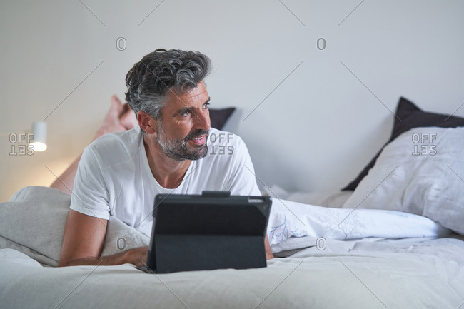 Smiling middle aged bearded male in casual clothes lying on bed and browsing laptop while resting in cozy bedroom in evening