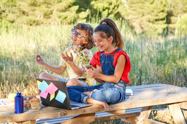 A ten year old boy and girl sitting at a wooden table in the field where there is a computer, flowers, fruit, snack. Dressed in denim and colorful T-shirts.