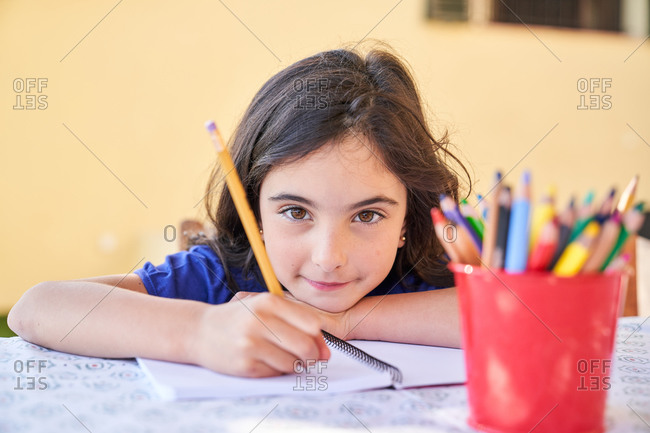 Positive school aged girl looking at camera and smiling while sitting at table and drawing with crayons in copybook during free time