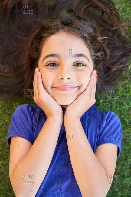 From above of happy preteen girl with wavy brown hair keeping hands on cheeks and looking at camera while lying on green grass