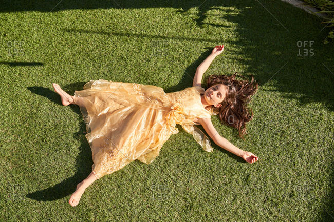 From above of peaceful relaxed little girl in beautiful lace dress lying on green grass and enjoying sunny summer day in garden