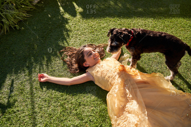 High angle of happy little girl in beautiful dress lying on green grass and laughing while playing with fluffy dog during summer day in garden