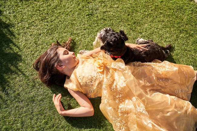 High angle of happy little girl in beautiful dress lying on green grass while playing with fluffy dog during summer day in garden
