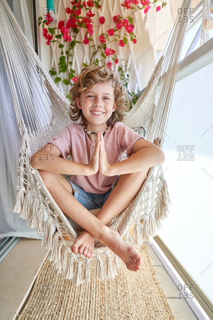 Calm barefoot child looking at camera in casual wear sitting in hammock with crossed legs and prayer hands above wicker carpet on balcony with potted plant in daylight