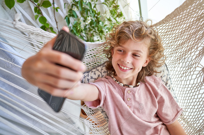 From above of cheerful child with curly hair taking selfie on cellphone while resting in hammock near climbing plant in daylight