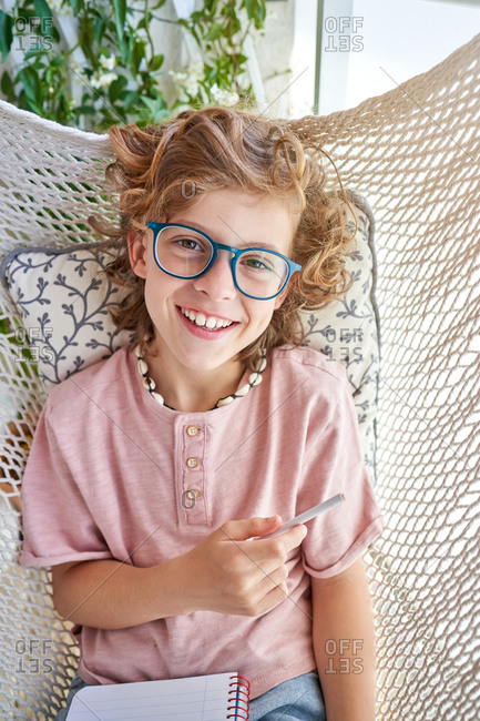 Happy boy in eyewear and casual clothes sitting looking at camera in hammock with pencil and journal while doing homework in apartment