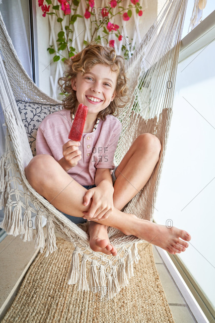 From above of barefoot blond boy resting in hammock with crossed legs while eating tasty fruit ice and looking away on balcony in sunlight