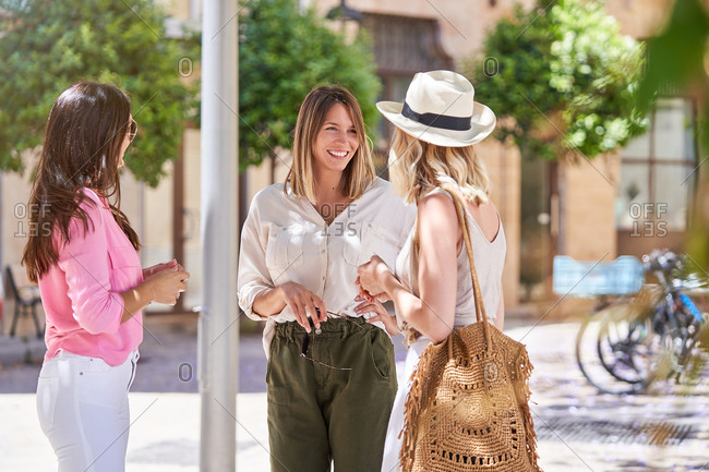 Trendy adult females in light summer clothes meeting on sunlit street in old town and chatting happily