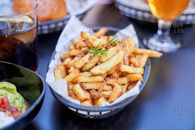 From above of black basket with French fries surrounded by snacks and beverages in cafe