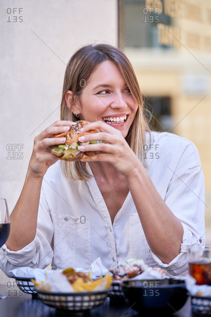 Cheerful adult female in white shirt having juicy burger for meal while sitting at cafe table on street smiling away to friend