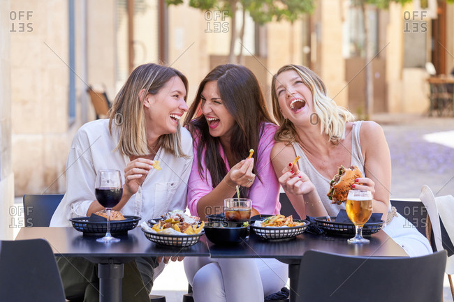 Group of trendy beautiful adult females laughing out loud while sharing delicious snacks with alcoholic drinks in sidewalk cafe