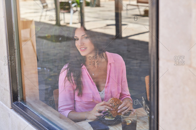 Through window of smiling brunette in pink shirt having delicious burger while smiling away in modern cafe