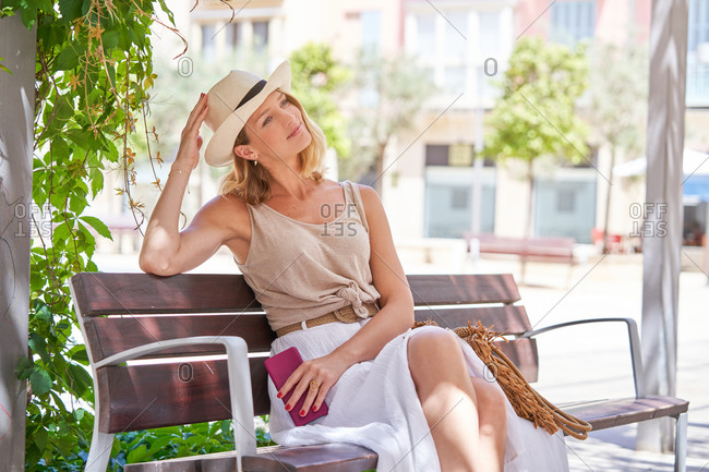 Trendy casual female in hat and skirt browsing smartphone while resting on wooden bench in bright sunny day