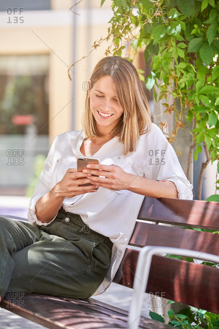 Trendy casual blond female browsing smartphone while resting on wooden bench in bright sunny day