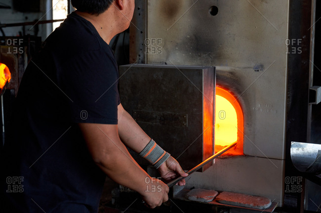 Crop back view of man holding blowpipe and melting glass in hot furnace in workshop