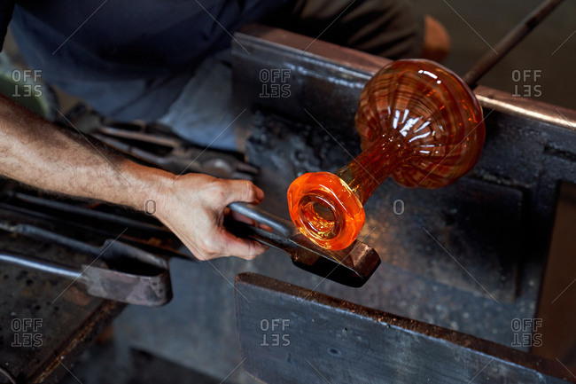 Faceless craftsman heating piece of molten glass on blowpipe while working in manufacture studio
