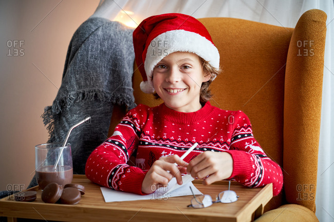 Cheerful child in Santa hat sitting in armchair with pencil in front of table tray with glass of chocolate drink and drinking tube near choco pies and looking at camera