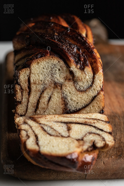Delicious homemade bread with chocolate and banana babka flavor placed on wooden table in kitchen on black background
