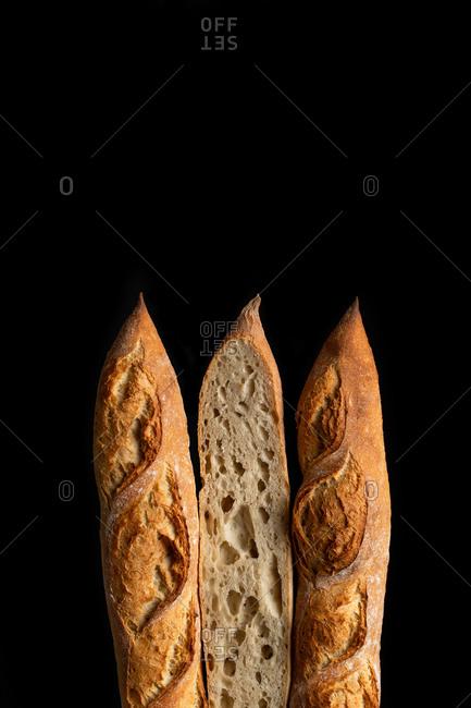 Tasty crunchy baguette in bakery on black background